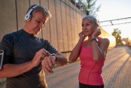 Ett äldre par med träningshörlurar som tränar löpning.