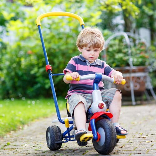 I början är det bra att använda en styrstång på trehjulingen för säker åkning.